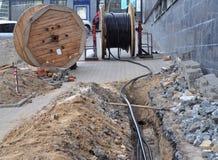 Hölzerne Spule der elektrischen Leitung und der Glasfasern im Graben auf die Straße Lizenzfreie Stockbilder