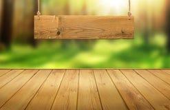 Hölzerne Tabelle mit hängendem Holzschild auf grünem Wald verwischte Hintergrund Stockfotografie