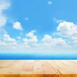 Hölzerne Tischplatte auf blauem Meerwasser und hellem Sommerhimmelhintergrund Stockfotos