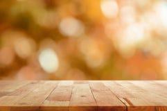 Hölzerne Tischplatte auf braunem bokeh Zusammenfassungshintergrund Stockfotos