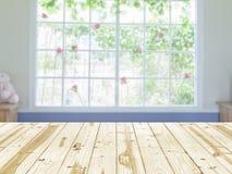 Hölzerne Tischplatte auf undeutlichem Hintergrund des Fensterinnenraumes Lizenzfreies Stockfoto
