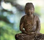 Hölzerner Buddha auf grünem Wald Stockfotos