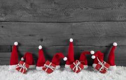Hölzerner grauer Weihnachtshintergrund mit roten Sankt-Hüten und -geschenken Lizenzfreies Stockfoto