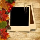 Hölzerner Hintergrund mit Herbstlaub und Rahmen für Foto Lizenzfreies Stockbild