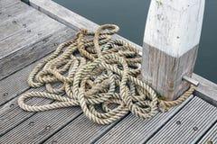 Hölzerner Pier mit Schiffspoller und langem Seil Stockbild