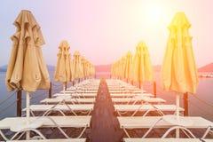 Hölzerner Pier mit sunbeds und Sonnenschirmen Stockfotos