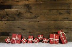 Hölzerner rustikaler Hintergrund mit roten Weihnachtsgeschenken Stockbilder