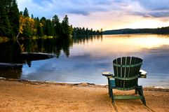 Hölzerner Stuhl am Sonnenuntergang auf Strand Lizenzfreie Stockfotografie