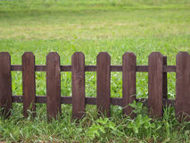 Hölzerner Zaun auf grünem Gras Lizenzfreie Stockfotografie