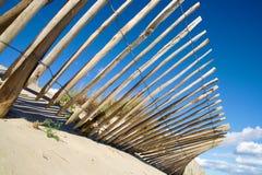 Hölzerner Zaun auf Strand mit dem Verbiegen des blauen Himmels Stockfoto