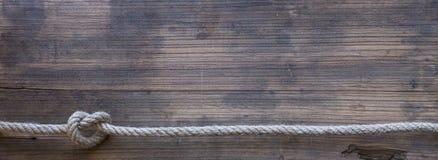 Hölzernes Brett mit einer rauen Beschaffenheit und einem Seil Stockfotografie