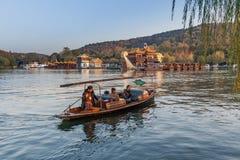 Hölzernes Erholungsboot des traditionellen Chinesen mit Schiffer Stockfoto