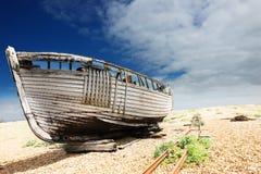 Hölzernes Fischerboot verließ, um und Zerfall auf dem Schindelstrand bei Dungeness, England, Großbritannien zu verrotten Lizenzfreie Stockfotos
