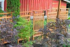 Hölzernes Gitter, welches das rote Scheunen-Fechten umfasst Lizenzfreies Stockfoto