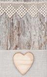 Hölzernes Herz auf dem Spitzegewebe und dem alten Holz Lizenzfreie Stockfotografie