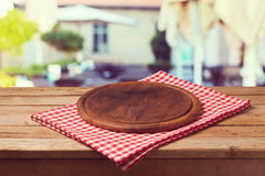 Hölzernes rundes Brett auf Tischdecke über Restauranthintergrund Stockfoto