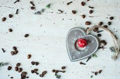 Hölzernes Weihnachtsspielzeug auf dem Tisch Herz, Kaffeebohnen und Gewürze Rustikaler Weihnachtshintergrund Lizenzfreie Stockfotos