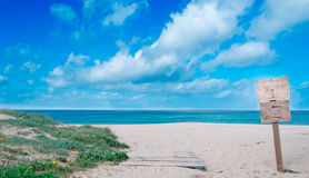 Hölzernes Zeichen am Strand in Sardinien Lizenzfreie Stockfotos