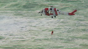 HM Coastguard helicopter with a Crew Member on its winch stock video