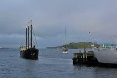HMCS Sackville的船尾与帆船和乔治海岛的在背景中在一个多云夏日 免版税库存图片