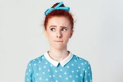 Hmm με επιτρέψτε να σκεφτώ απομονωμένο στούντιο που πυροβολείται στο γκρίζο υπόβαθρο του χαριτωμένου redhead κοριτσιού με να κοιτ Στοκ Εικόνα