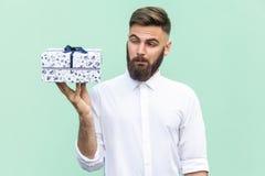 Hmm τι είναι αυτό! Το γενειοφόρο άτομο που εξετάζει το κιβώτιο δώρων και θέλει πάρα πολύ ανοικτό Στοκ Φωτογραφίες