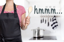 Hmm cook holding wooden spoon background concept Royalty Free Stock Photography
