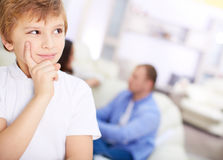 Hmm. Portrait of pensive boy on background of his parents Royalty Free Stock Photography