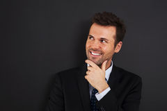 Hmm, it's interesting.. Pensive young businessman looking on side Royalty Free Stock Photos