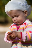 Hmm, what is it?. A portrait of a little girl who is holding a plastic bottle cap in her hands for the very first time. How interesting Stock Image