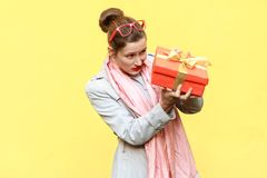 Hmm what is it! Cunning woman looking at gift box and want too o. Pen. Yellow background. Studio shot Royalty Free Stock Image