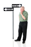 Hmm.  Which Way?. A senior man near My Way and Highway signs, contemplating which direction he'll take.  On a white background Stock Images