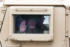 HMMWV-Militärfahrzeug mit dem Soldaten, der heraus das Fenster schaut Lizenzfreie Stockbilder