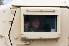 HMMWV-Militärfahrzeug mit dem Soldaten, der heraus das Fenster schaut Stockbild