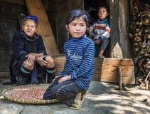 Hmong部落祖母休息她的有她的两个孙的房子外的在一个小村庄, Sapa,越南 库存图片