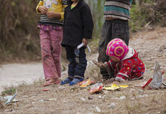 Hmong child eating candy on the dirty ground in Dong Van rocky plateau. Royalty Free Stock Images