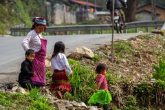 Hmong ethnic minority family Vietnam. Ha Giang, Vietnam - March 18, 2018: Family from the Hmong ethnic minority walking on a field near a street in the mountains royalty free stock photography