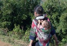 Hmong kvinna som bär hennes barn i hennes ryggsäck. Sapa. Vietnam Arkivfoto