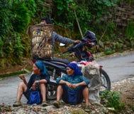 Hmong kvinnor som sitter på den lantliga vägen arkivbilder