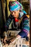 Hmong kvinnor som väver hampa för att göra tyget för kläderna som hon bär royaltyfri fotografi