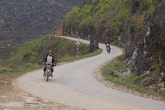 Hmong minority men driving motorcycles on a mountain pass in Dong Van Karst Plateau Geopark Royalty Free Stock Photography