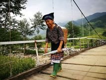 Hmong old woman walking on a wooden hanging bridge. Mu Cang Chai, Vietnam - Sep 16, 2016: Hmong old woman walking on a wooden hanging bridge from her village to Royalty Free Stock Photography