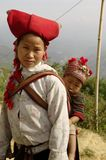 Hmong red Sapa  woman and baby. Nearly SAPA, City of North Vietnam. A woman of the ethnic (minority) Hmong Red pompoms with her baby in the back. She wears her Stock Photography