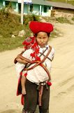 Hmong red Sapa  woman and baby. Nearly SAPA, City of North Vietnam. A woman of the ethnic (minority) Hmong Red pompoms with her baby in the back. She wears her Stock Photos