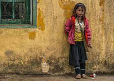 Hmong schoolgirl standing against yellow wall. Royalty Free Stock Photography