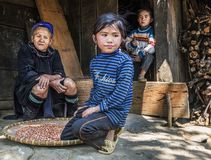 Hmong tribe grandmother resting outside her house with her two grandchildren in a small village, Sapa, Vietnam stock images