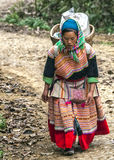 Hmong woman with loaded basket on her back comes around the bend Royalty Free Stock Images