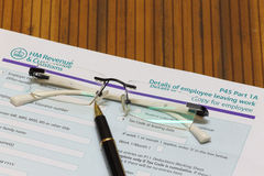 HMRC UK P45 form and eye glass. HMRC UK P45 form for employee leaving work Royalty Free Stock Photo