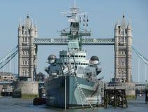 HMS Belfast som förtöjas av tornbron London Royaltyfri Bild