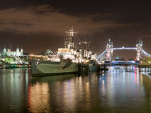 HMS Belfast and Tower Bridge. Night scene along the River Thames showing HMS Belfast and Tower Bridge Stock Photo